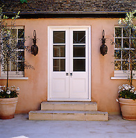 The entrance to the guest house is flanked by a pair of olive trees in terracotta pots to match the colour of the painted plaster of the wall