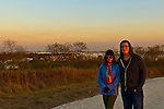 South Merrick, New York, U.S. 29th October 2013. Greg, from Merrick, and his mother walk on the trail through Levy Park and Preserve during sunset on the First Anniversary of Superstorm Sandy hitting New York. Long Island's South Shore marshland park, which closed for months due to Sandy's devastation, shows some recovery from the wind and flood damage inflicted on the entire eastern seaboard of America's East Coast.