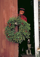 Woman placing Christmas wreath, holiday, tradition.