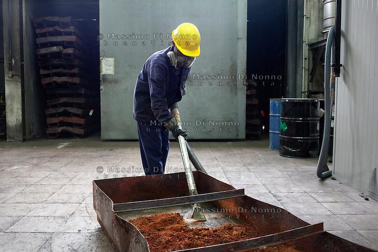 Arezzo: un operaio all'interno dello stabilimento Chimet aspira il materiale uscito da un forno. L'azienda recupera metalli preziosi (oro, platino, palladio, iridio, argento) da materiali di scarto come catalizzatori di marmitte, batterie, contatti elettrici di cellulari, computer o materiali di scarto industriale.<br /> <br /> Arezzo: The Chimet company recovers precious metals (gold, platinum, palladium, iridium, silver) from waste materials such as catalysts, mufflers, batteries, electrical contacts to phones, computers or industrial waste materials.