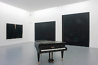 A grand piano stands in solitary isolation on the concrete floor of this gallery which displays a series of black artworks