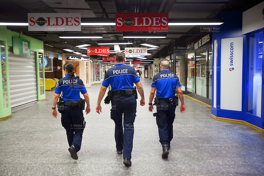 Switzerland. Geneva. Thee police officers patrol on feet at night the underground shopping mall of the railway station. Sign for sales season. The police woman and both policemen are wearing a ballistic vest, bulletproof vest or bullet-resistant vest which is an item of personal armor that helps absorb the impact from knives, firearm-fired projectiles and shrapnel from explosions, and is worn on the torso. Soft vests are made from many layers of woven or laminated fibers and can be capable of protecting the wearer from small-caliber handgun and shotgun projectiles. The policewoman haa a two-way radio which is a radio that can both transmit and receive (a transceiver). A two-way radio (transceiver) allows the operator to have a conversation with other similar radios operating on the same radio frequency (channel). Two-way radios are available with hand-held portable configurations. Hand-held radios are often called walkie-talkies or handie-talkies. They all carry  a Glock pistol which is a semi-automatic pistol designed and produced by Glock Ges.m.b.H. 9.07.12 © 2012 Didier Ruef?.