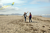 USA, Washington State, Long Beach Peninsula, International Kite Festival, young woman runs on the beach with her kite