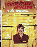 ARGENTINA, Bariloche, smiling lady with stack of packed chocolates at the Turista Chocolate store.