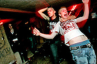 Javier Morales, guitar player for suburban Illinois band the Heretics (center left) and James Gregory, dance during a punk concert in the basement of the White House in Woodstock, Illinois.  The White House was a small suburban residential home rented by a group of 20-somethings in Woodstock, Illinois, a distant northwestern suburb of Chicago.  For about a year, the renters of the house staged punk-rock concerts in the house's small basement, without the approval of the neighborhood, local government, or police.  .