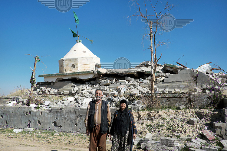 An elderly couple from the Kakai religious minority stands in front of Kakai place of worship destroyed by ISIS militants.
