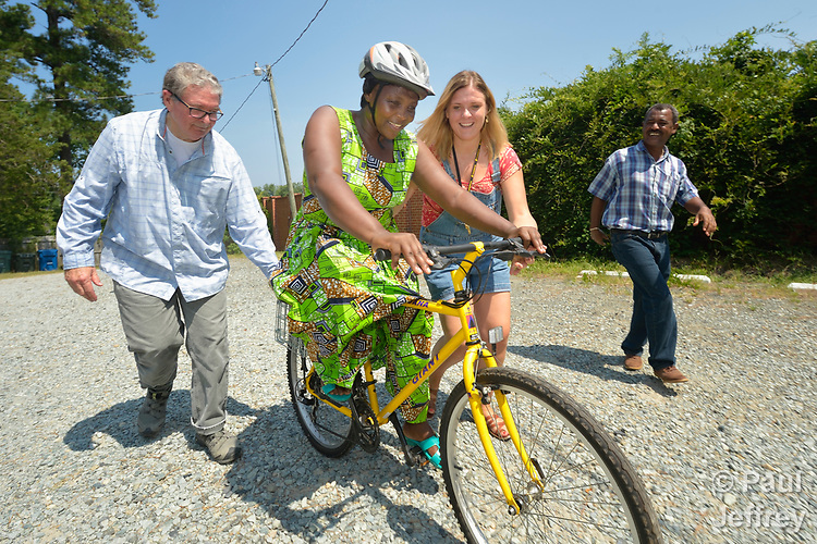 Evanis Gatunzi, a refugee from Rwanda, rides a bike for the first time in Durham, North Carolina, on July 22, 2017. She's helped by Greg Garneau, a volunteer who coordinates the refugee bike program for the Durham Bicycle Co-op, and Monique Lohmeyer, a case manager for Church World Service. In the background, Yosef Birhane, a refugee from Eritrea, cheers her on.<br /> <br /> Church World Service resettles refugees in North Carolina and throughout the United States.<br /> <br /> Photo by Paul Jeffrey for Church World Service.