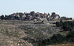A picture taken from the West Bank city of Hebron on February 7, 2017 shows a view of the Kiryat Arba Jewish settlement on the outskirts of the Palestinian city. Israel's parliament passed a contentious law late Monday that allows the state to seize land privately owned by Palestinians in the West Bank and grant the properties to Jewish settlements for their exclusive use. Photo by Wisam Hashlamoun