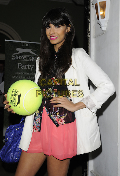 Jameela Jamil .At the Slazenger Party, The House of St. Barnabas, Greek Street, London, England, UK, 23rd June 2011..half length pink  skirt white jacket blazer  back print shirt hand on hip holding oversized tennis ball .CAP/CAN.©Can Nguyen/Capital Pictures.