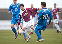 Arbroath's Ross Chisolm tries to get past Queen of the South's Nicky Clark.