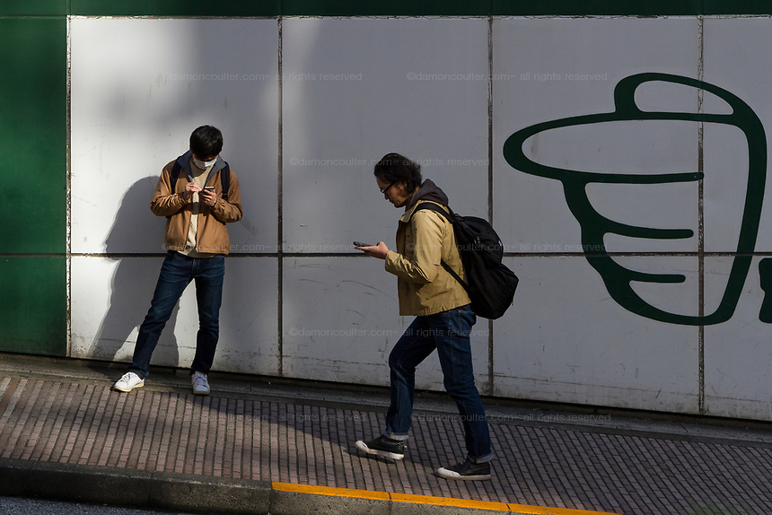 Using using smartphones as they walk and wait in the streets of Shibuya, Tokyo, Japan. Wednesday November 21st 2018