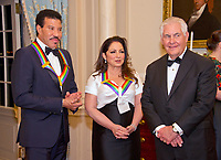 Lionel Richie, left, and Gloria Estefan, center, two of the five recipients of the 40th Annual Kennedy Center Honors speak with United States Secretary of State Rex Tillerson, right, as they wait to pose for a group photo following a dinner hosted by Secretary  Tillerson in their honor at the US Department of State in Washington, D.C. on Saturday, December 2, 2017.  The 2017 honorees are: American dancer and choreographer Carmen de Lavallade; Cuban American singer-songwriter and actress Gloria Estefan; American hip hop artist and entertainment icon LL COOL J; American television writer and producer Norman Lear; and American musician and record producer Lionel Richie.  <br /> Credit: Ron Sachs / Pool via CNP /MediaPunch