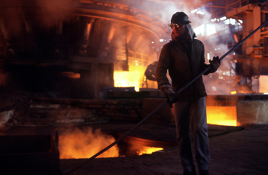 An employee of CSN Steel in Volta Redonda, Brazil, guides molten metal as it flows through a trough from one of the plant's 2,400-degree Celsius ovens. The state-owned plant and others will be privatized as part of Brazil's new economic plan