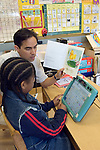 Oakland CA Developmentally disabled primary school student and teacher working with AAC (Alternative augmentative communication) devices in special education classroom, learning to write   MR