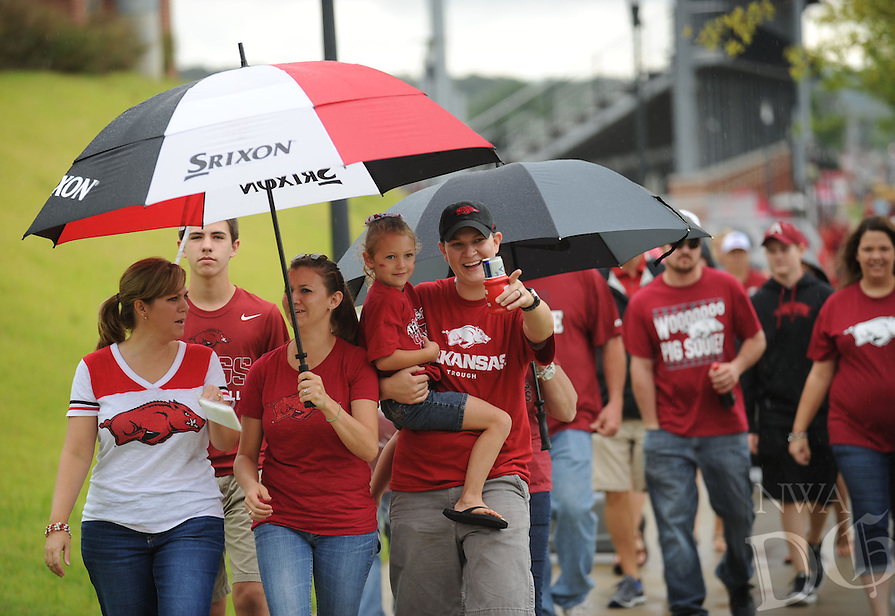 STAFF PHOTO ANDY SHUPE - Fans walk beneath umbrellas along Razorback Road prior to the start of the University of Arkansas' football game with Nicholls State Saturday, Sept. 6, 2014, at Razorback Stadium in Fayetteville.