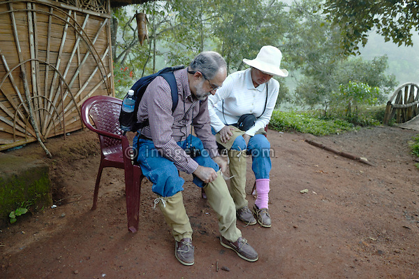 India, Kerala, Periyar/Kumily, Periyar Tiger Reserve.  A couple of senior western tourists in the Periyar Tiger Reserve putting on some leech socks for protection before going on a guided game-watching tour through the forest. No releases available.