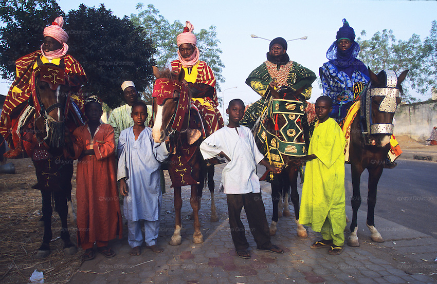 Local chiefs mounted on horseback with traditional clothes get ready for the last day of the Fantasia..The Durbar Fantasia, is the moment where The Husa residents of Kano wear traditional dress, their local leaders and chiefs mount horses, and together with their militias display allegiance and homage to their leader, the Emir of Kano. This takes place after Ramadan. The Emir is Kano's State official political and economic feudal leader, everyone seeks to be in his pleasure, otherwise they reap the consequences..Kano is the largest Muslim Husa city, under the feudal, political and economic rule of the Emir. Kano and the other eleven northern states are under Islamic Sharia Law which is enforced by official state apparatus including military and police, Islamic schools and education, plus various volunteer Militia groups supported financially and politically by the Emir and other business and political bodies. 70% of the population live below the poverty line. Kano, Kano State, Northern Nigeria, Africa