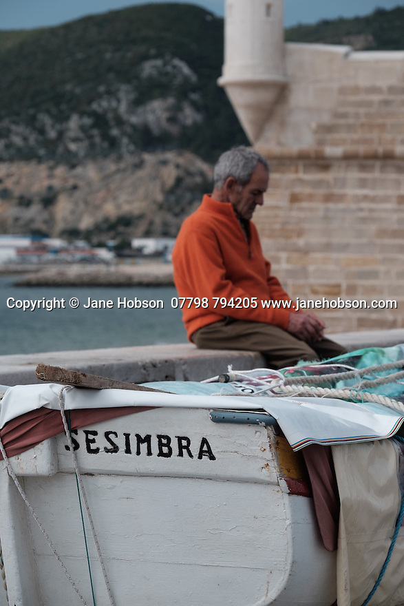 Sesimbra, Lisbon, Portugal. 22.03.2015. Fisherman by his boat in Sesimbra, a seaside town south of Lisbon, Portugal.  © Jane Hobson.