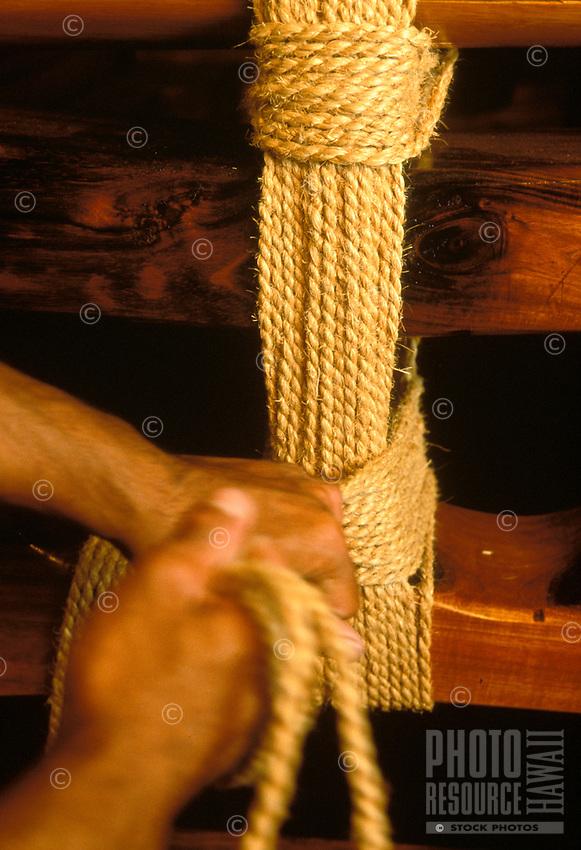Hands lashing cordage on Polynesian voyaging canoe, Hawaiiloa