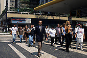 Sao Paulo, Brazil. Businessmen and women crossing the street in front of a drugstore.