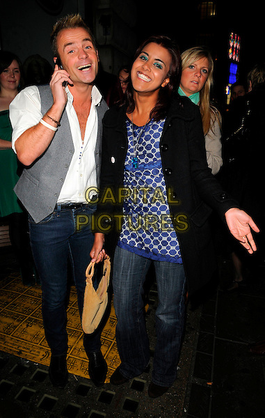JULIAN BENNETT & POOJA SHAH.The Paper Club Brit Awards afterparty, 68 Regent Street, London, England..February 20th, 2008.after party brits full length black jacket silver grey gray polka dot top jeans denim waistcoat white shirt mouth open talking on mobile phone  .CAP/CAN.©Can Nguyen/Capital Pictures.