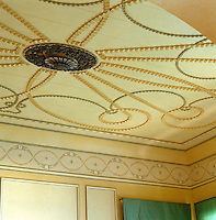 An elaborately carved ceiling rose with rippled carved ribbons decorate the living room ceiling