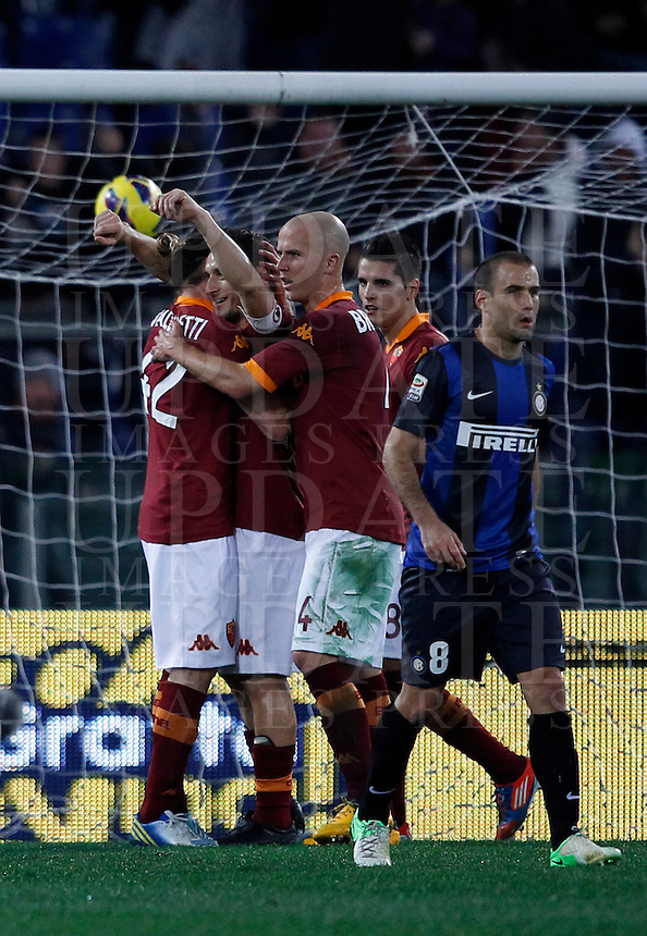 Calcio, Serie A: Roma vs Inter. Roma, stadio Olimpico, 20 gennaio 2013..AS Roma forward Francesco Totti, second from left, is hugged by teammates after scoring on a penalty kick, as FC Inter forward Rodrigo Palacio, of Argentina, right, reacts during the Italian Serie A football match between AS Roma and FC Inter at Rome's Olympic stadium, 20 January 2013..UPDATE IMAGES PRESS/Isabella Bonotto