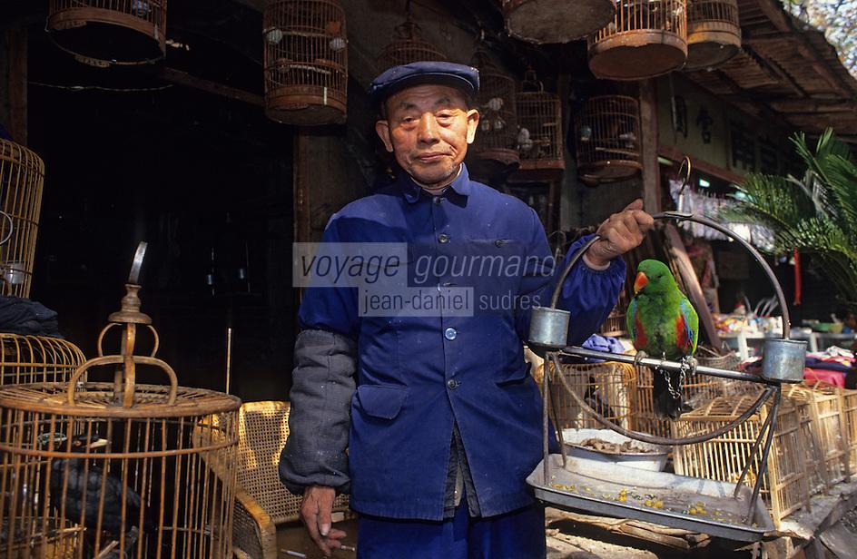 Asie/Chine/Jiangsu/Nankin/Quartier du temple de Confucius: Marché aux oiseaux - Marchand présentant un perroquet<br /> PHOTO D'ARCHIVES // ARCHIVAL IMAGES<br /> CHINE 1990