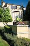 sunny late afternoon image of colorful pink and purple summer annuals spilling out of an interesting raised planter box built in to a stucco wall that terraces down the back yard of a European-style estate house with blue summer sky above