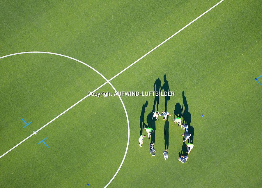 Schattenspiel: EUROPA, DEUTSCHLAND, HAMBURG (EUROPE, GERMANY), 09.11.2014: Schattenspiel, Fussballmannschaft macht vor dem Spiel Aufwaermgymnastik im Kreis. Billtalstadion