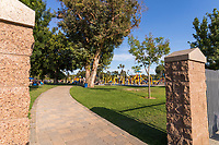 A horizonally-crpped view of one of the entrances to South Gate Park: block columns frame a paver pathway that curves under mature trees while leading to a giant playground full of children.