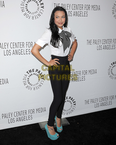 NAYA RIVERA .at The PaleyFest 2011 Panel for Glee held at The Saban Theater in Beverly Hills, California, USA, March 16th,2011..full length skinny thin high waisted jeans jeggings black white shirt bow tie  polka dot turquoise peep toe shoes wedges suede platform tattoo on ankle                       .CAP/RKE/DVS.©DVS/RockinExposures/Capital Pictures.