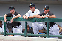 Chicago White Sox instructors Doug Sisson (left), Vance Law (right), and Charlotte Knights manager Joel Skinner (center) watch the action from the dugout during the game against the Pawtucket Red Sox at BB&T Ballpark on August 8, 2014 in Charlotte, North Carolina.  The Red Sox defeated the Knights  11-8.  (Brian Westerholt/Four Seam Images)