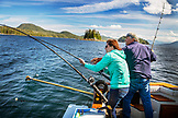ALASKA, Ketchikan, with help from Captain Tony, one woman attempts to reel in a fish while fishing the Behm Canal near Clarence Straight, Knudsen Cove along the Tongass Narrows