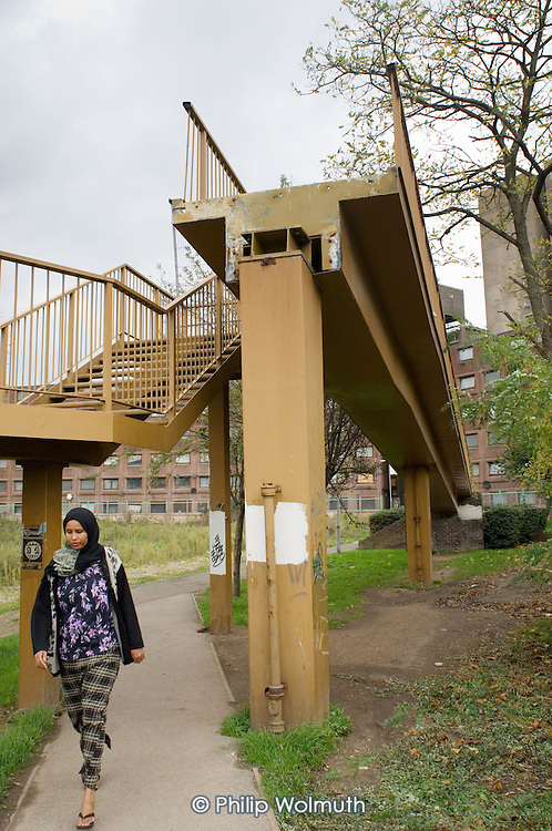 A woman wearing a headscarf walks beneath a partly demolished walkway on the Stonebridge Estate, in the London Borough of Brent. The estate is managed by the Stonebridge Housing Action Trust (HAT).