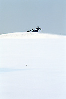 A reclining sculpture by Henry Moore is dramatically outlined against the snowy landscape