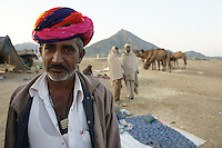 man selling camels on camel fair in holy city Pushkar, Rajastan, India. Multi-color turbans are worn on special occasions like the camel fair.