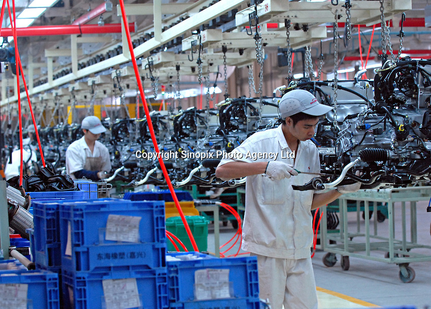 A worker on the engine production line of the Honda Accord at the new Guangzhou Honda Automobile Co. Ltd. factory. The plant built at a cost of 140 million US$ is one of the most advanced car plants in the world. It has a state of the art production line as well as the world's first total water re-cycling sytem..