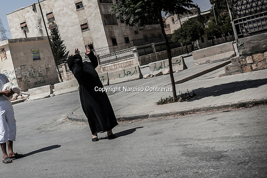 A Muslim woman claims with the hands up to the air to stop the shelling to the Syrian army aircraft that flies over her head at the residential Hanano neighborhood in north of Aleppo City.