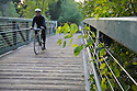 A cyclist riding over Stevens Creek. Mountain View, California, USA