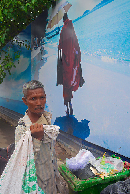 A man and collecting garbage for recycling in a cart in the street of Phnom Penh, in front of a street a Photo Mural, Cambodia