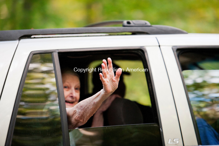 SOUTHBURY, CT - 26 September 2013-092613EC07--   A woman who lives at a home along Georges Hill Road in Southbury waves to the media as she is driven off the property Thursday afternoon. Law enforcement agencies from several towns seized over two dozen dogs there. Erin Covey Republican-American.