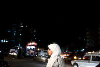Amena, one of the youngest Muslim Sister of the Nasr City's area, hands out leaflets to drivers stuck in traffic just outside of El Taba quarter, a poor area of Cairo. Egypt, June 2012.