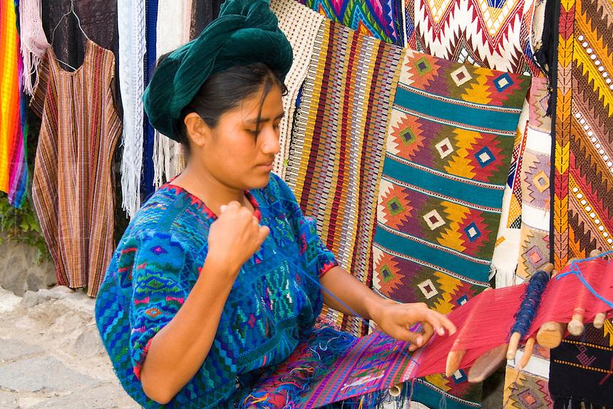 Woman using hand loom weaving artwork outside in Villa Santa Catarina in remote Lake Atitlan Guatemal