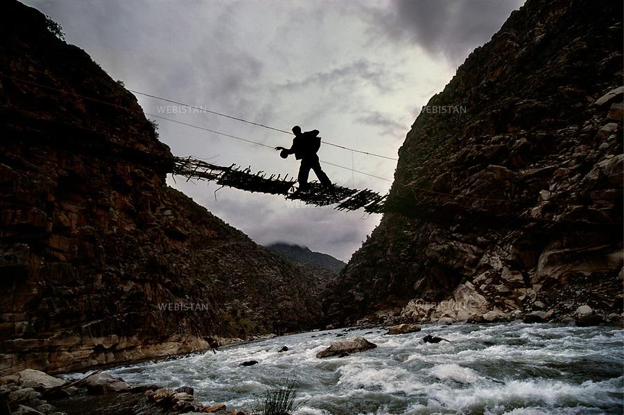 Afghanistan. Province of Nouristan. 1985. A bridge suspended off the Konar river.<br /> <br /> Afghanistan. Province du Nouristan. 1985. Un pont suspendu au-dessus de la rivi&egrave;re Konar.