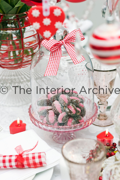 The centrepiece of this festive dining table is a bowl of sugared dates stuffed with pink marzipan