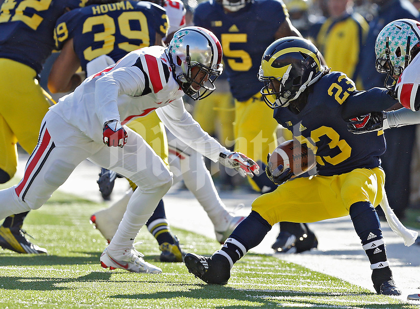 Ohio State Buckeyes defensive back Vonn Bell (11) tackles Michigan Wolverines wide receiver Dennis Norfleet (23) during a punt return during their college football game at Michigan Stadium in Ann Arbor, Michigan on November 30, 2013.  (Dispatch photo by Kyle Robertson)