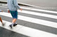 Children walking across a zebra crossing on a city street, Paris, France.