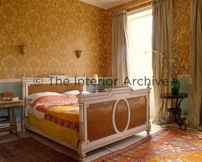 A vintage French bed is covered with a colourful patchwork quilt that echoes the golden colour of the wallpaper