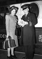 "Mr Donald White, ""The Man from Cook's"" assists a woman traveller on the Golden Arrow train at Victoria station.<br /> April 1948"